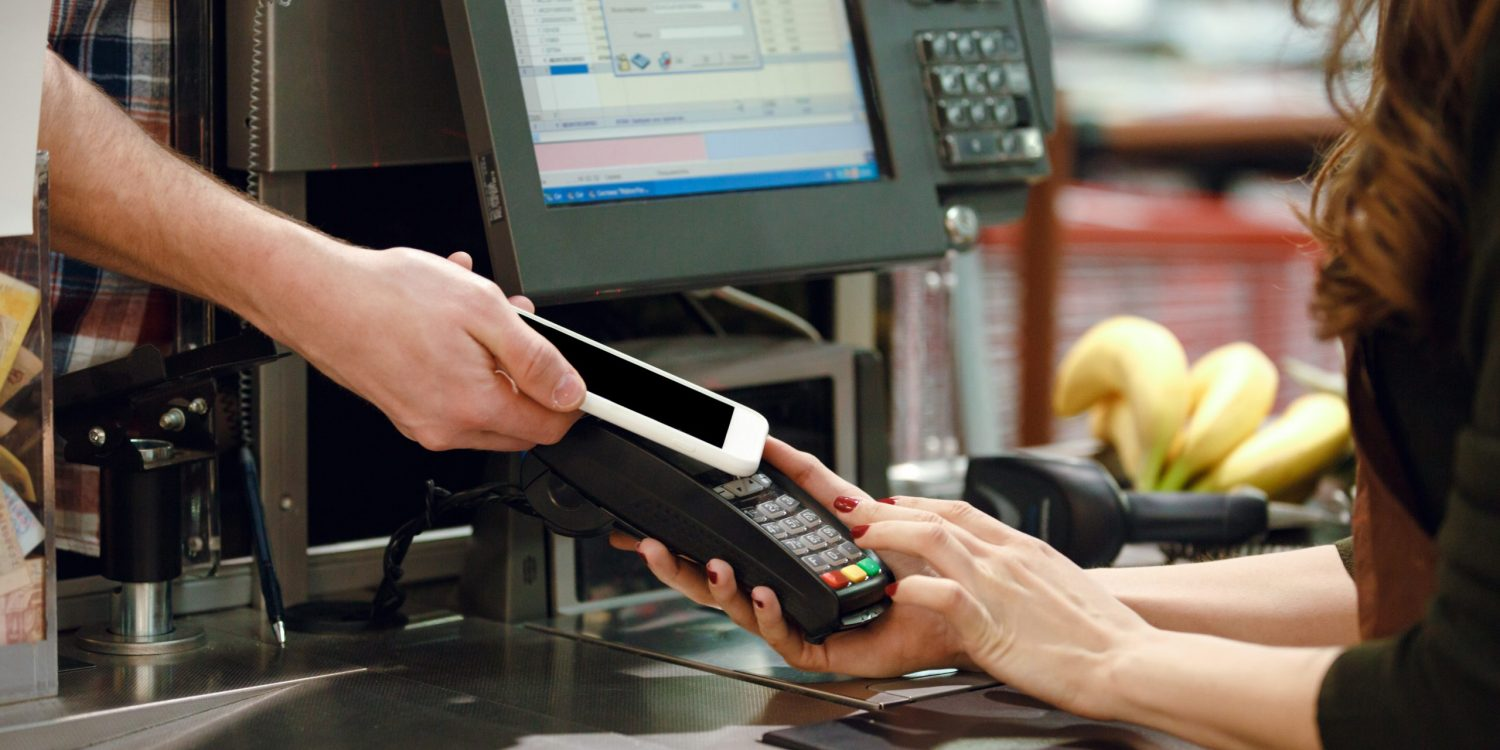 Cropped image of cashier woman on workspace in supermarket shop create payment with mobile phone app.