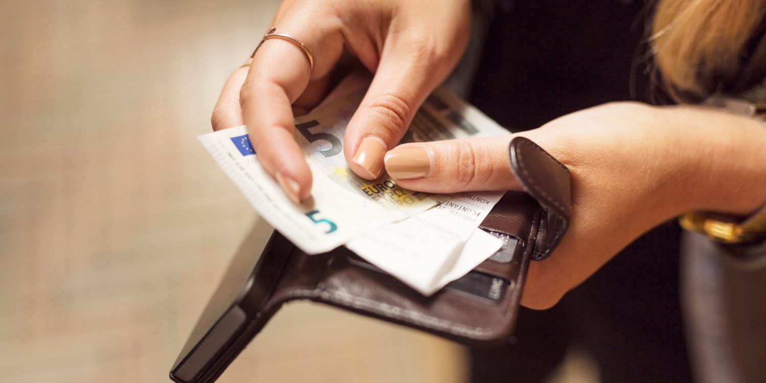 Woman holding open wallet with banknotes, receipts and cell phone